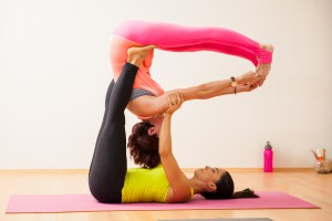 Two strong young women demonstrating an acrobatic yoga pose in a yoga studio ** Note: Soft Focus at 100%, best at smaller sizes