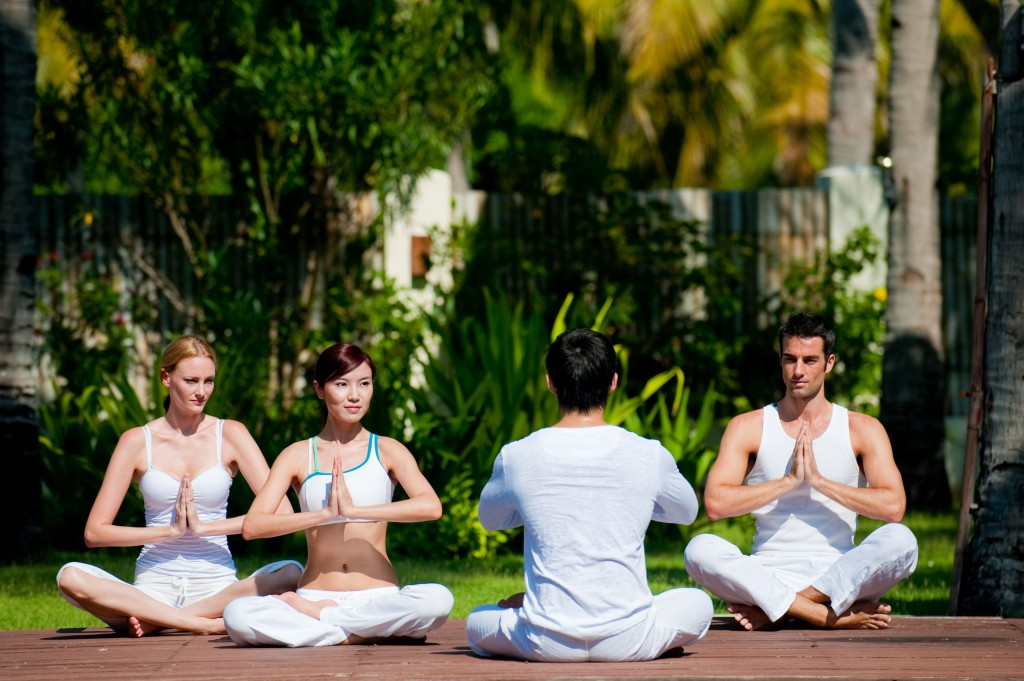 A group of friends practicing yoga outdoors